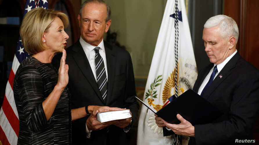Vice President Mike Pence swears in Betsy DeVos as U.S. education secretary at the Eisenhower Executive Office Building at the White House in Washington, Feb. 7, 2017. With them is DeVos' husband, Dick DeVos.