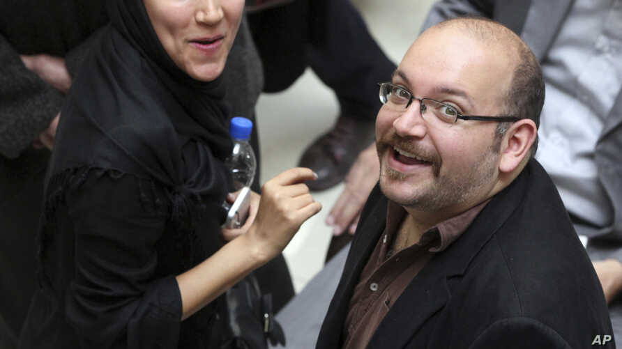 Jason Rezaian (R), an Iranian-American correspondent for The Washington Post, and his wife Yeganeh Salehi, an Iranian correspondent for the Abu Dhabi-based newspaper The National, attend a presidential campaign of President Hassan Rouhani in Tehran,