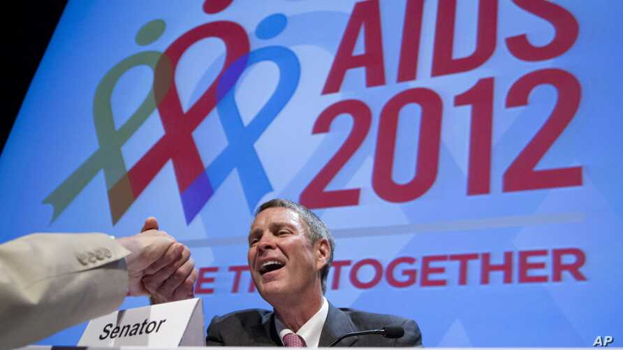 Former Senate Majority Leader Bill Frist shakes hands with a member of the audience at the XIX International AIDS Conference in Washington, July 25, 2012.