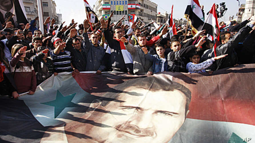 Syrians hold a large poster depicting Syria's President Bashar Assad during a rally in Damascus, Syria. Syria signed an Arab League initiative Monday that will allow Arab observers into the country as part of peace deal that aims to end the nation's