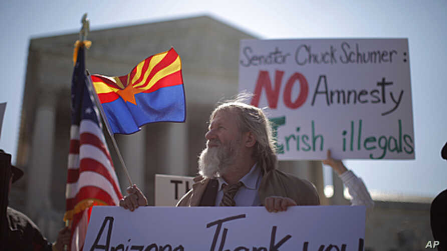 """Charles Balogh demonstrates in front of the Supreme Court in Washington as the court holds a hearing on Arizona's """"show me your papers"""" immigration law, April 25, 2012."""