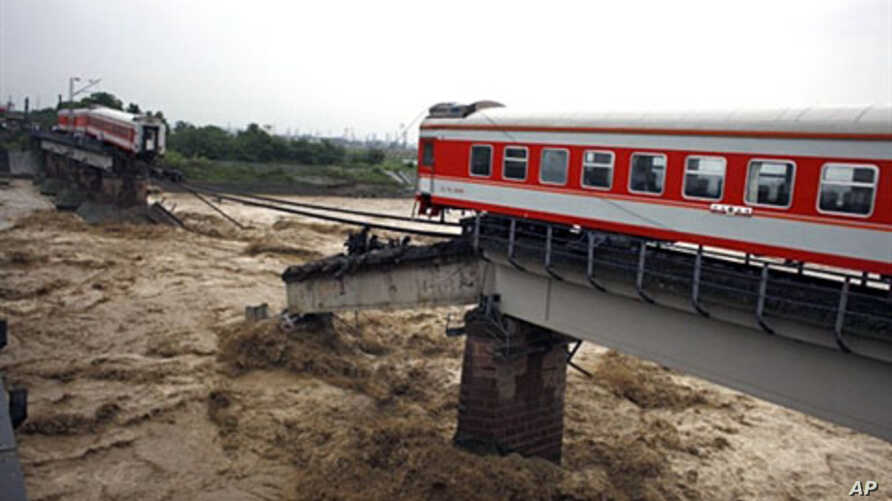 The two ends of a train remain on a bridge after passengers were evacuated near Guanghan in southwest China's Sichuan province, one of the areas hit hard by flooding , 19 Aug 2010
