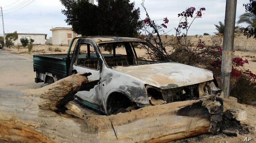 A burned truck is seen outside al-Rawdah mosque in Bir al-Abed, northern Sinai, Egypt, a day after attackers killed hundreds of worshippers, Nov. 25, 2017. Friday's assault was Egypt's deadliest attack by Islamic extremists in the country's modern hi