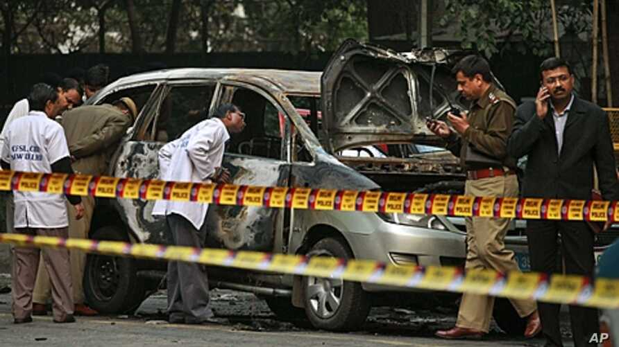 Indian police forensics experts investigate the scene after an explosion tore through a car belonging to the Israel Embassy in New Delhi, India, February 13, 2012.