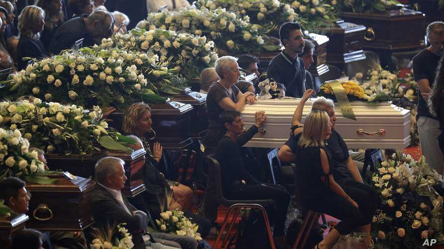 Relatives sit by a small white coffin as they attend a funeral service for some of the victims of a collapsed highway bridge, in Genoa's exhibition center Fiera di Genova, Italy, Aug. 18, 2018.
