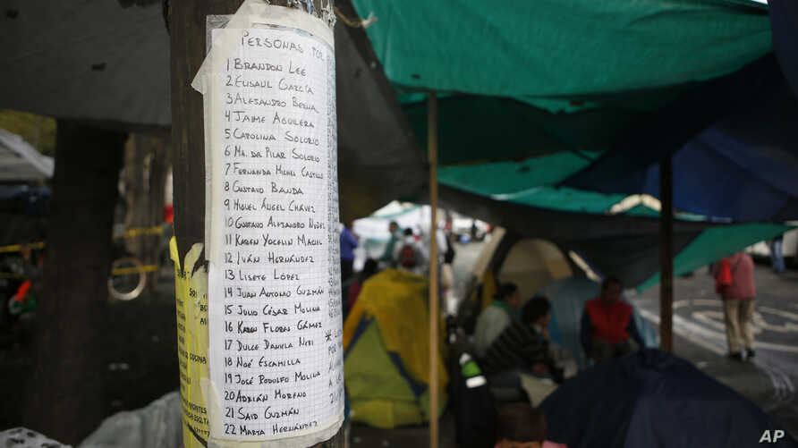 A list of missing persons is posted outside a quake-collapsed seven-story building in Mexico City's Roma Norte neighborhood, Sept. 22, 2017. Mexican officials promise to keep searching for survivors as rescue operations stretch into a fourth day.