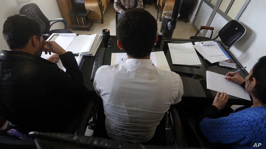 In this April 3, 2018 photo, a Syrian 19-year-old former member of the Islamic State group, who declined to be identified, sits opposite a panel of three judges, in the courtroom of a Kurdish-run terrorism court, in Qamishli, north Syria.