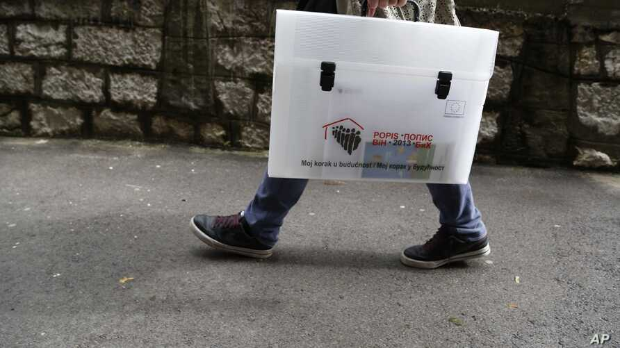 """Bosnian pollster with carrying case labelled """"2013 census, my step into the future,"""" Sarajevo, Oct. 1, 2013."""
