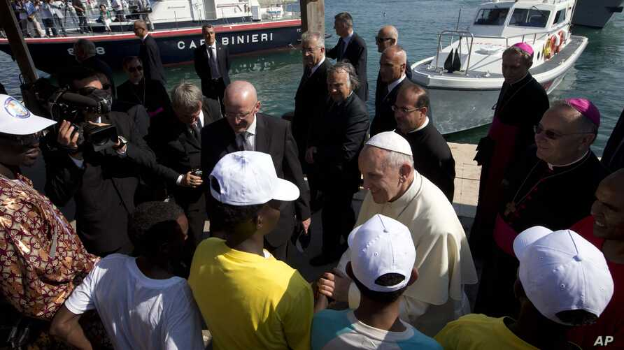 FILE - Pope Francis speaks to migrants during his visit to the island of Lampedusa, southern Italy, July 8, 2013. The pontiff traveled there to pray for migrants lost at sea.
