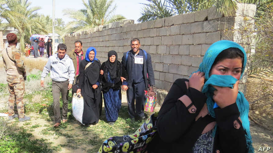 Iraqi pro-governement forces help people displaced from Islamic State (IS) group controlled areas close to Fallujah, on February 7, 2016.