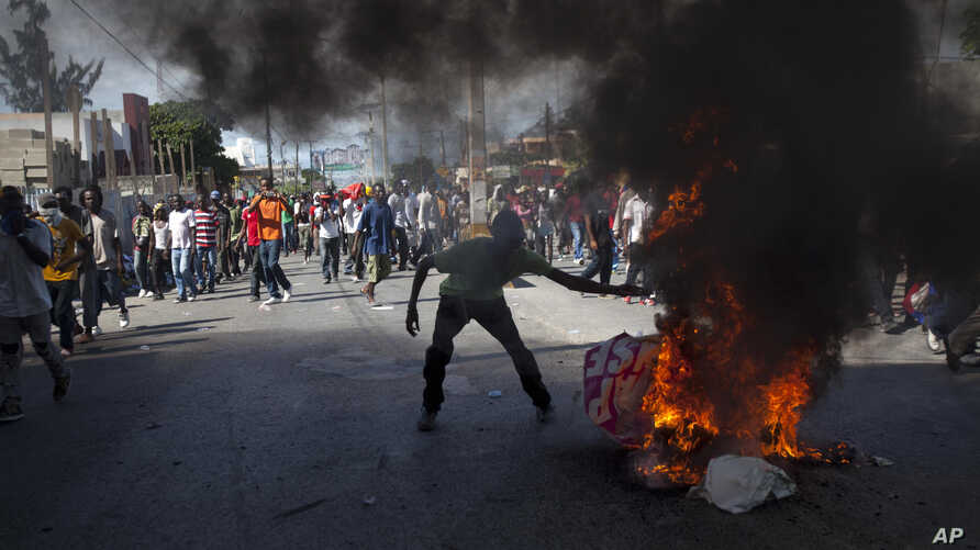 A protester burns a picture of Haiti's President Michel Martelly as demonstrators call for Martelly's departure from office on the anniversary of the Vertières battle in Port-au-Prince, Nov. 18, 2013.