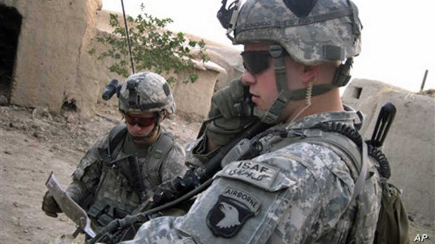 Soldiers from the US 101st Airborne Division's 1st Battalion, 5 Lt. Cory Donohoo, right, makes a radio call while Pfc. Michael Miles reads a map as troops search a home in Senjeray, Kandahar province, Afghanistan, 7 Sept. 2010.