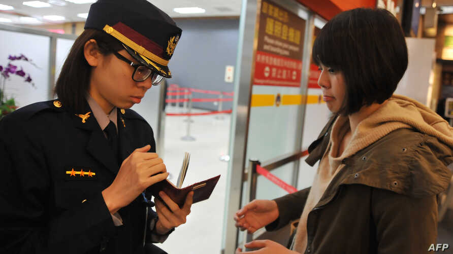An airport security officer (L) checks a passenger's passport and boarding pass at Taipei Songshan Airport on March 10, 2014.