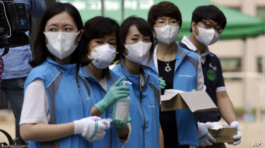 South Korean health workers from a community health center wearing masks as a precaution against MERS, Middle East Respiratory Syndrome, virus, wait to check examinees' temperature and to sanitzie their hands at a test site for a civil service examin...