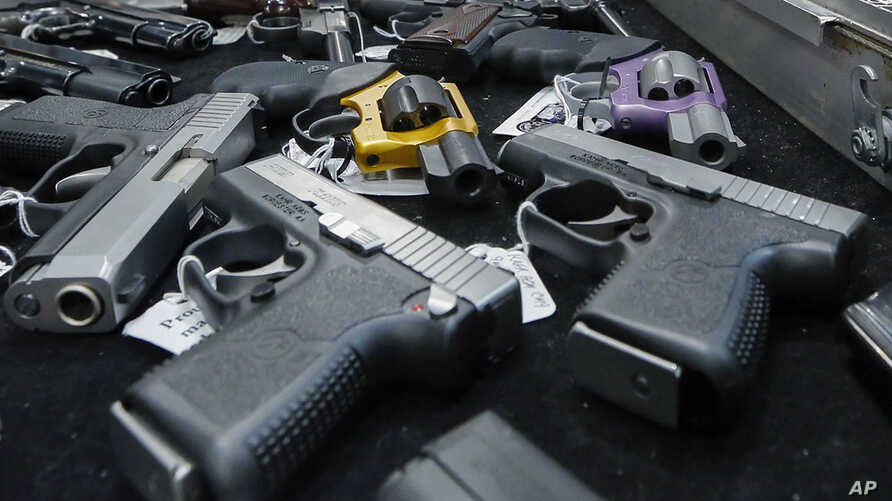 FILE - Handguns are displayed on a vendor's table at an annual gun show in Albany, N.Y., Jan. 26, 2013.