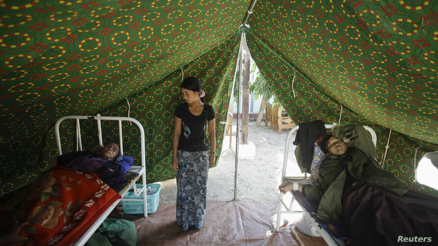 Injured people are treated outside a damaged hospital in Thabeik Kyin township, Burma, November 12, 2012.