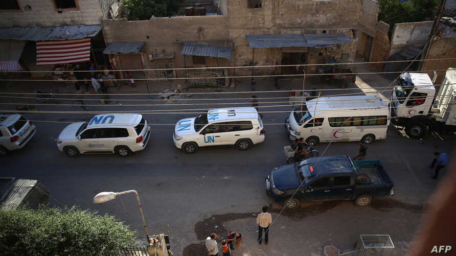 Vehicles of a UN and SARC aid convoy, with food, nutrition, health and other emergency items, enter the rebel-held town of Douma, east of the Syrian capital Damascus, on June 10, 2016.