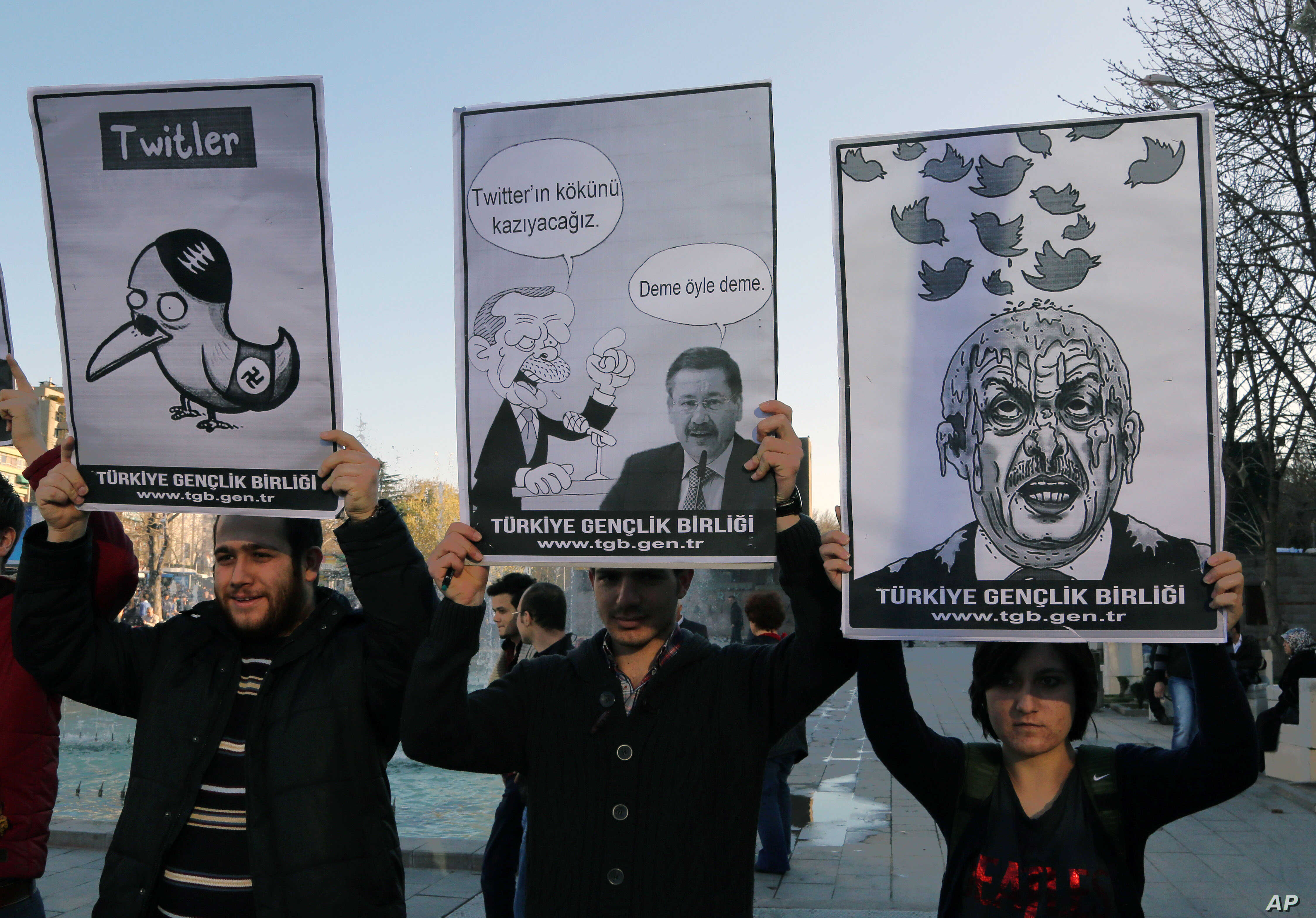 Members of the Turkish Youth Union hold cartoons depicting Turkey's Prime Minister Recep Tayyip Erdogan during a protest against a ban on Twitter, in Ankara, March 21, 2014.