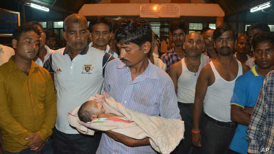 A man holds the lifeless body of his child outside Baba Raghav Das Medical College Hospital in Gorakhpur, in the northern Indian state of Uttar Pradesh, Aug. 11, 2017.