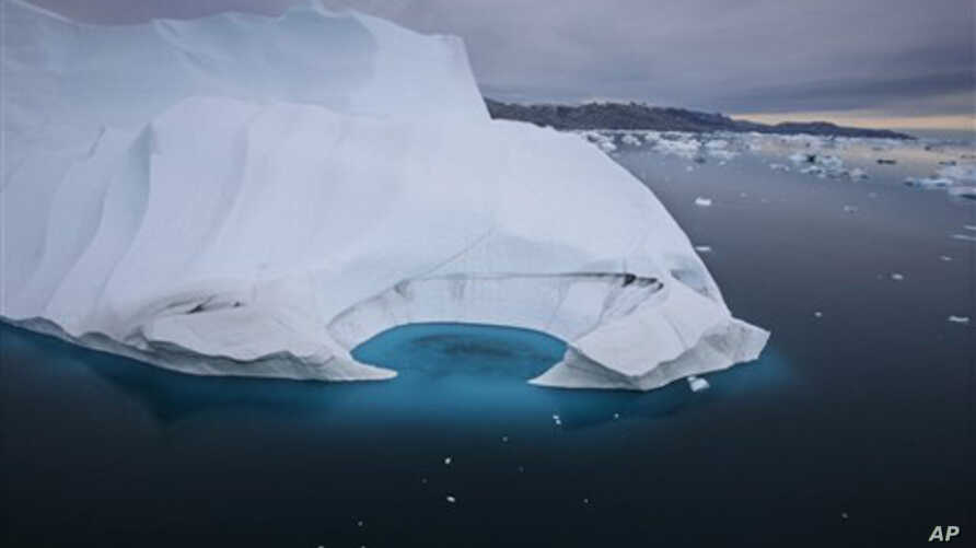 In this July 19, 2007 file photo, an iceberg is seen melting off the coast of Ammasalik, Greenland.  A new assessment of climate change in the Arctic shows the ice in the region is melting faster than previously thought and sharply raises projections