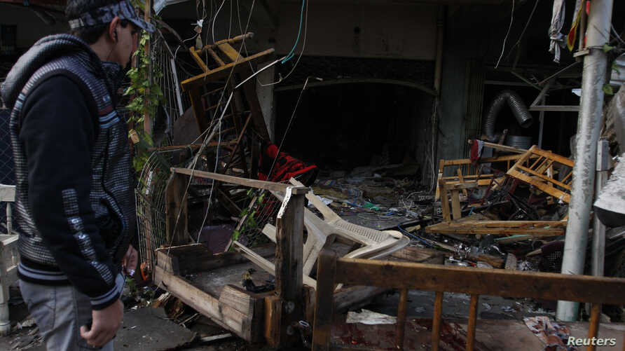 A man looks at the site of a bomb attack at a cafe in Baghdad's al-Bayaa district, Nov. 21, 2013.