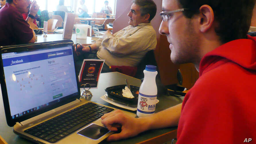 In this April 18, 2013, photo sophomore Mike Ziehr looks at his computer in the student union at the University of Wisconsin-Madison.