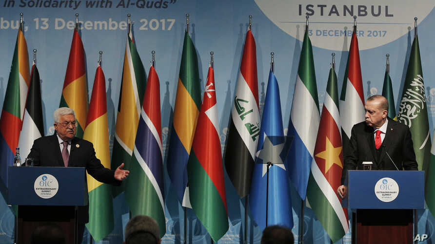 Turkey's President Recep Tayyip Erdogan, right, watches as Palestinian President Mahmoud Abbas, left, gestures as he talks during the closing news conference following the Organisation of Islamic Cooperation's Extraordinary Summit in Istanbul, Wednes