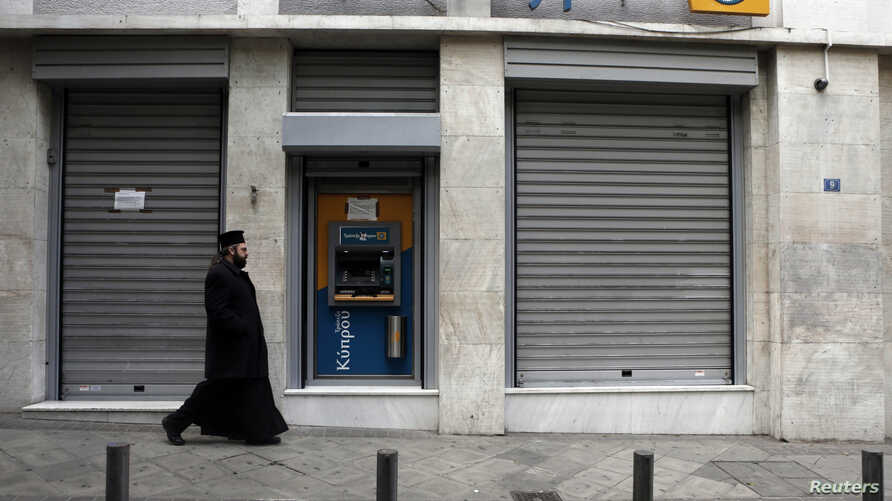 A Greek Orthodox priest walks a branch of Bank of Cyprus in Athens March 19, 2013.