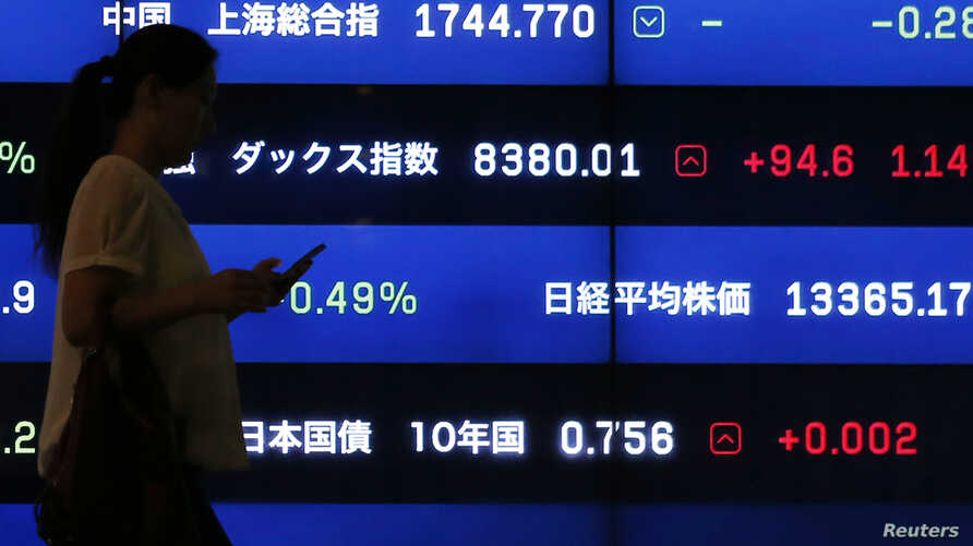 FILE - A woman walks past a screen showing market indices in Tokyo. The International Monetary Fund says that for advanced economies, debt has risen to more than 107 percent of their national economic output, while Japan is almost at 250 percent.