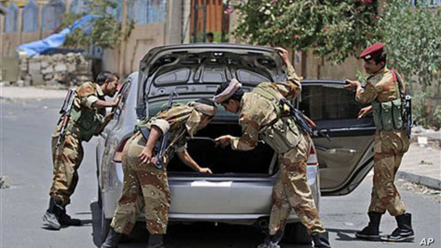 Yemeni army soldiers check a car in Sana'a, Yemen, as government troops try to recapture areas held by Islamic militants, June 9, 2011