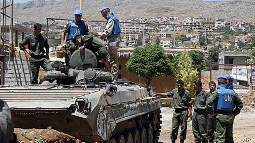 United Nations (U.N.) observers examine a Syrian army tank during a field visit to the al-Zabadani area, near Damascus, May 6, 2012. Al-Zabadani is one of the locations where protests against the regime of Syrian President Bashar al-Assad were being