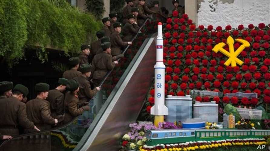 """North Korean soldiers ride escalator past a model of the Unha Rocket alongside so-called """"Kimjongilia"""" flowers at an exhibition in Pyongyang, Feb. 17, 2013."""
