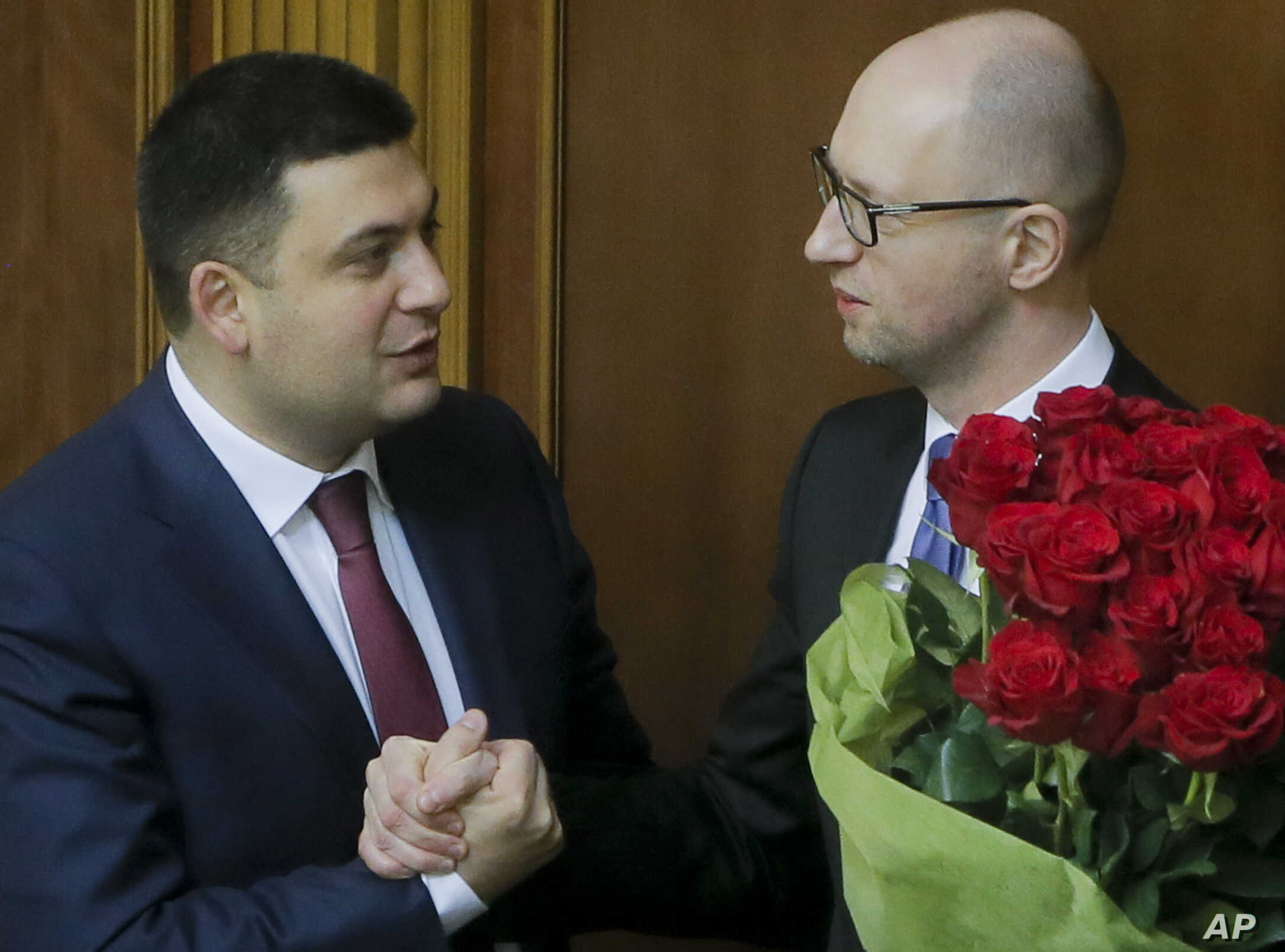 FILE- - Prime Minister Arseniy Yatsenyuk, right, and parliament speaker Volodymyr Groysman celebrate after Yatsenyuk was appointed the Prime Minister during the opening first session of the Ukrainian parliament in Kyiv, Nov. 27, 2014.