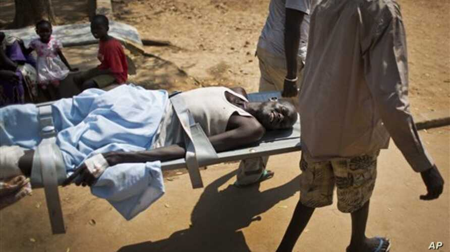 In this Saturday Dec. 28 2013 file photo, a man with a gunshot wound in his leg is carried by stretcher inside the Juba Military Hospital in Juba, South Sudan. Battles between government forces and rebel fighters continue, and aid officials say the i