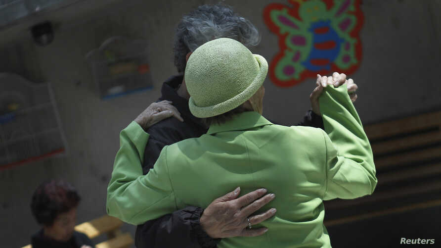 FILE - Patients with Alzheimer's and dementia dance inside the Alzheimer Foundation in Mexico City, April 19, 2012.