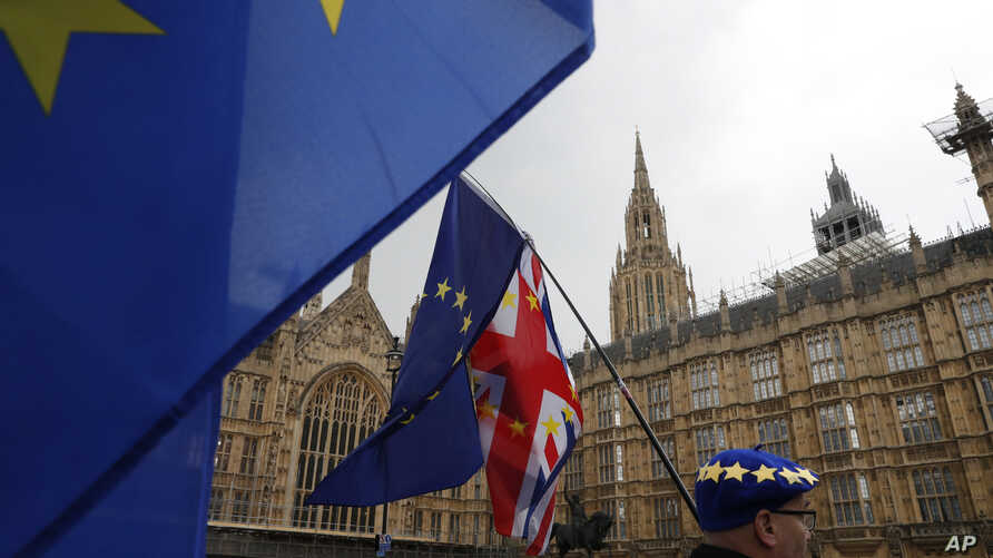 Anti Brexit demonstrators hold up their flags opposite the Houses of Parliament in London, April 3, 2019.