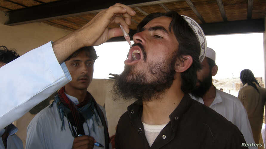 A man, who fled the military offensive against the Pakistani militants in North Waziristan, receives polio vaccination drops upon his arrival in Bannu in Khyber-Pakhtunkhwa province, Pakistan, June 22, 2014.