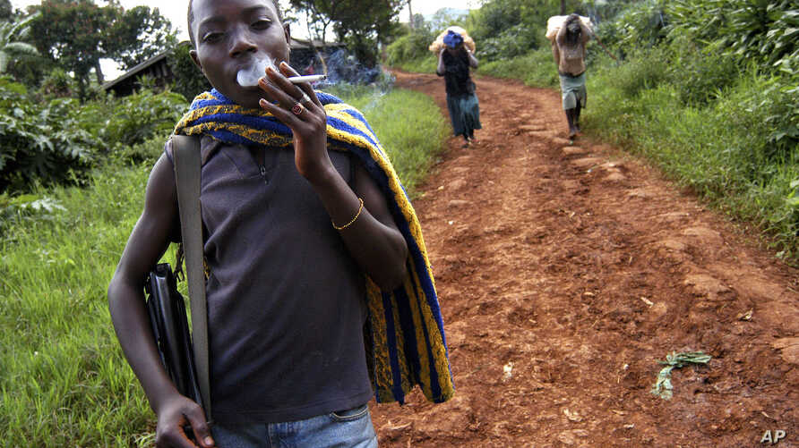 FILE - Ombeni Balihiamwabo,17, stands with his rifle outside a  military post in Nyangonbe, Democratic Republic of Congo.