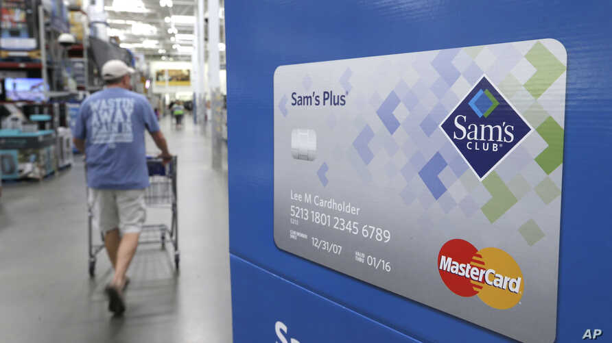 A customer walks past a sign promoting Sam's Club MasterCard credit cards at a Sam's Club store store in Bentonville, Ark., June 4, 2015.