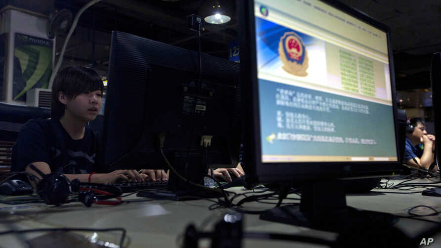 FILE - Computer users sit near a monitor display with a message from the Chinese police on proper online behavior, at an Internet cafe in Beijing, China, Aug. 19, 2013.