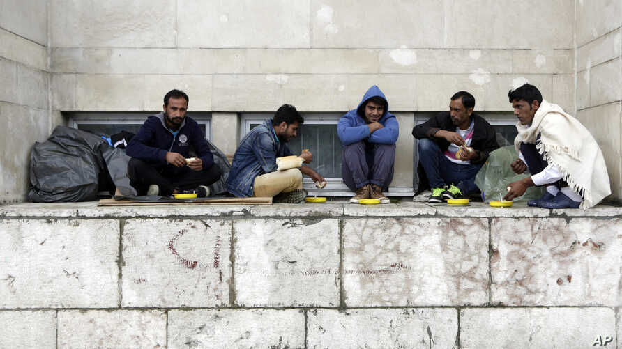 FILE - Migrants from Pakistan have their lunch in front of a railway station in Sarajevo, Bosnia, on June 19, 2018, as they wait for an opportunity to get to Croatia and Western Europe.