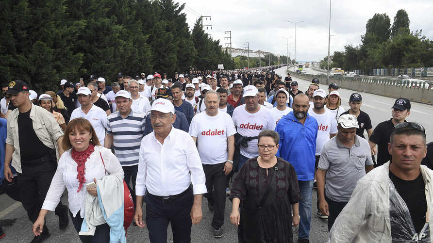 """Kemal Kilicdaroglu,foreground, second left, the leader of Turkey's main opposition Republican People's Party, walks with thousands of supporters on the 20th day of his 425-kilometer (265-mile) """" march for justice """" in Izmit, Turkey, Tuesday, July 4,"""