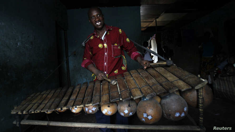 FILE - A son of Diabate Kalifa, a Balafon manufacturer, plays a Balafon at his father's workshop in Abobo.