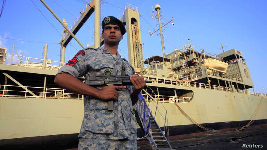 An Iranian soldier stands guard near Iranian Navy helicopter carrier Kharg at Port Sudan at the Red Sea State, October 31, 2012.