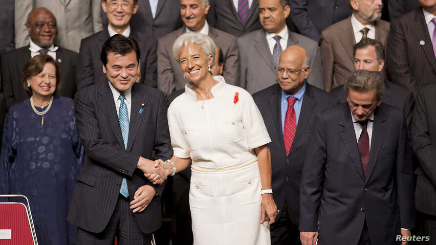 International Monetary Fund (IMF) Managing Director Christine Lagarde shakes hands with Japanese Finance Minister Koriki Jojima before posing for a group photograph in Tokyo October 12, 2012 during the semi-annual meetings of the IMF and World Bank.