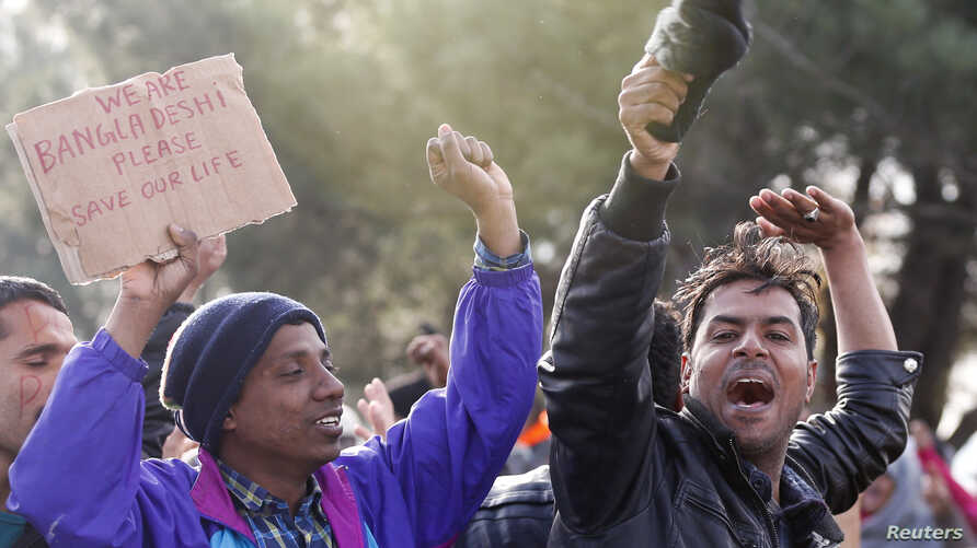 FILE - Migrants from Bangladesh shout 'Open the border!' as they protest while waiting to cross the border from Greece into Macedonia, near Gevgelija, Macedonia, Nov. 26, 2015.