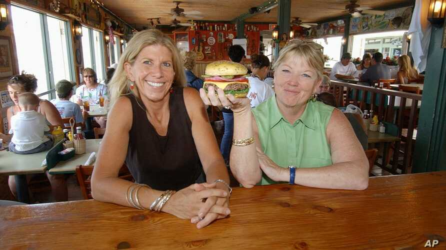 FILE - Cheeseburger in Paradise founders and co-owners Edna Bayliff, left, and Laren Gartner pose with one of their trademark burgers at their Lahaina, Hawaii, restaurant.