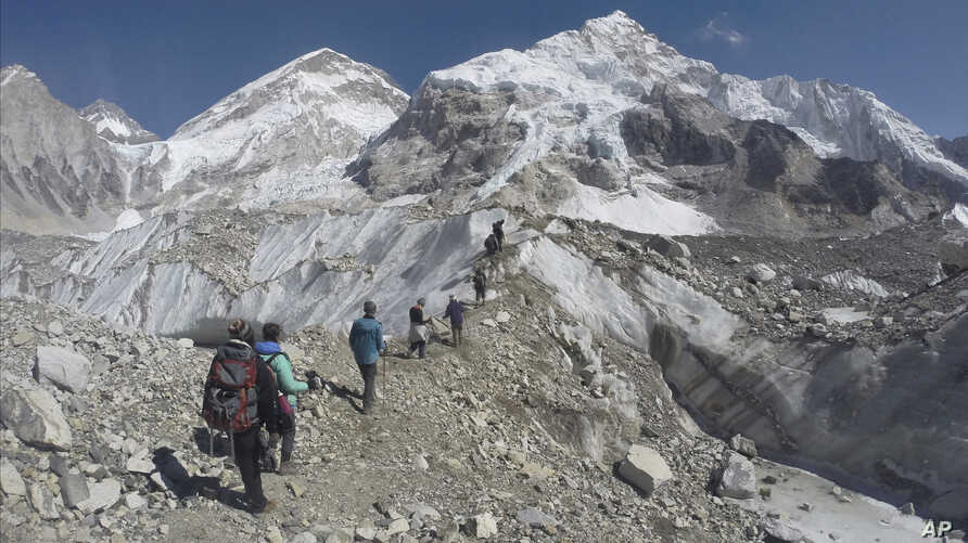 FILE - Climbers pass through a glacier at the Mount Everest base camp, Nepal, Feb. 22, 2016.