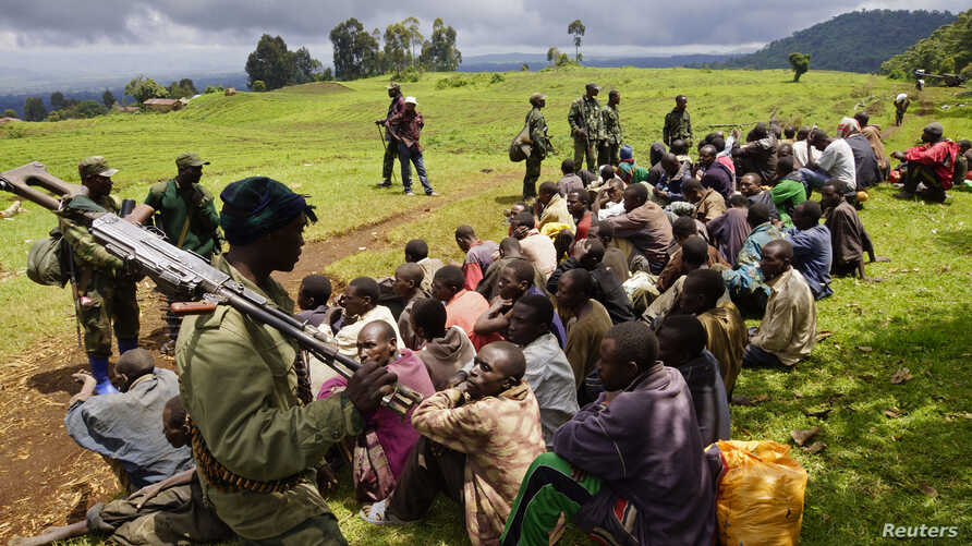 Congolese soldiers guard suspected M23 rebel fighters who surrendered in Chanzo village near the eastern town of Goma, Nov. 5, 2013.