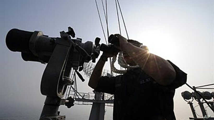 A crew member looks through binoculars on the aircraft carrier USS George Washington during a joint Navy exercise with South Korea in the Yellow Sea, 30 Nov 2010